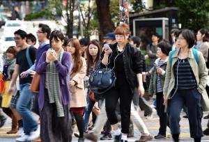 Pedestrians use their smartphones on a street in Tokyo,…