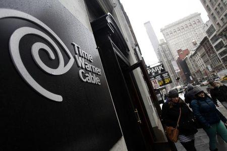 Pedestrians walk past a Time Warner Cable customer service center in New York