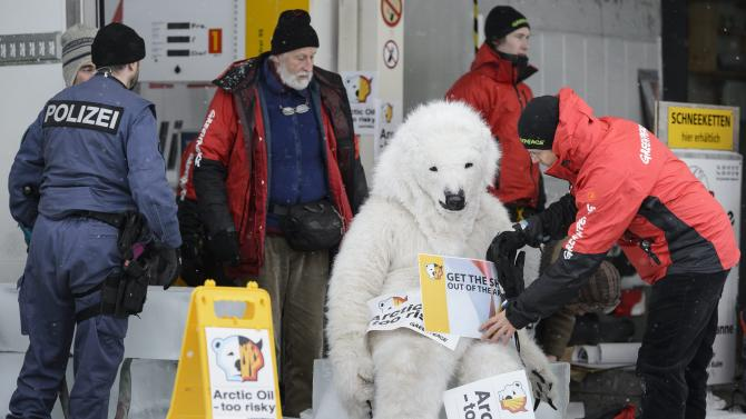 Police talks to Greenpeace activists who are demonstrating in a Shell petrol station on the sideline of the 43rd annual meeting of the World Economic Forum, WEF, in Wolfgang near Davos, Switzerland, Friday, Jan. 25, 2013. (AP Photo/Keystone, Laurent Gillieron)