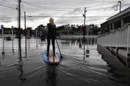 Zoe Jurusik, 20, paddle-boards down a flooded city street in the aftermath of Hurricane Sandy in Bethany Beach, Delaware, October 30, 2012. REUTERS/Jonathan Ernst