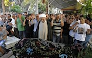 Mourners pray over the body of Hamad al-Moqdad, one of the Lebanese victims of a car bomb attack that killed dozens in a Beirut stronghold of Shiite group Hezbollah, during his funeral procession in the capital on August 16, 2013