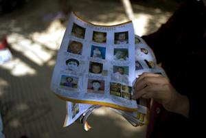 Ye Jinxiu, 59, displays pictures of missing children …
