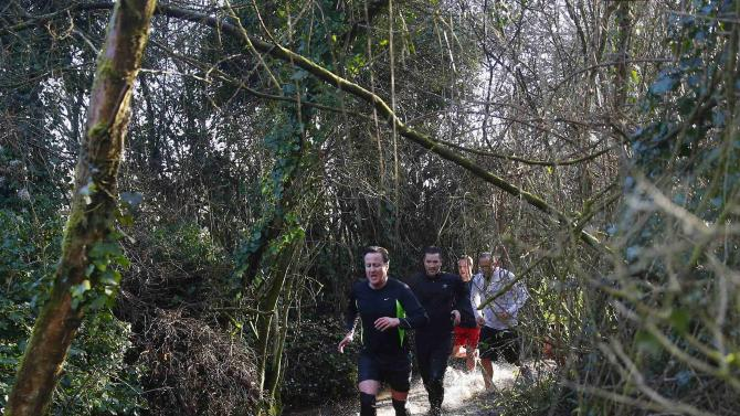 British Prime Minister Cameron competes in the Great Brook Run, a mile long course through water and mud, at Chadlington