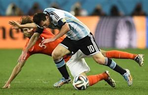 Blind of the Netherlands and Argentina's Messi fight for the ball during their 2014 World Cup semi-finals in Sao Paulo