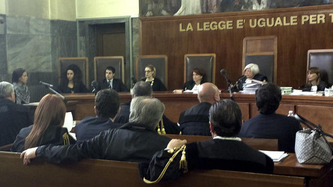 """Karima el-Mahroug, from Morocco, the woman at the center of a sex scandal involving former Italian Premier Silvio Berlusconi, is seen sitting in the witness stand at left speaking into a microphone as she testifies for the first time in the trial of three Berlusconi aides charged with recruiting her and other women for prostitution, in Milan's courthouse, Italy, Friday, May 17, 2013. El-Mahroug, known by the nickname Ruby Heart Stealer, has made carefully orchestrated statements to the media since the scandal broke but has never publicly given sworn testimony. Both she and Berlusconi deny having had sex. Prosecutors in Berlusconi's separate trial on charges of paying for sex with a minor and trying to cover it up say her testimony is unreliable and are relying on her sworn statements. Writing above judges reads in Italian """"The law is equal for all.""""(AP Photo/Luca Bruno)"""