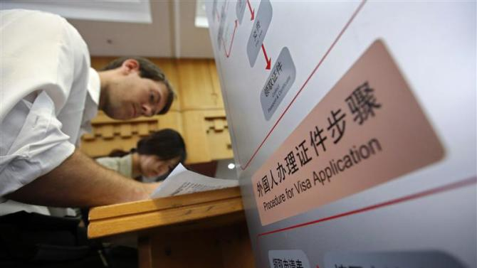 Foreigners fill up forms at Beijing's Exit & Entry Administration Service Center,