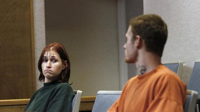 """FILE - In this Oct. 11, 2011 file photo, Holly Grigsby, left, looks at her boyfriend, David """"Joey"""" Pedersen, during an appearance in Yuba County Superior Court in Marysville, Calif. On Tuesday, July 15, 2014, a federal judge in Portland, Ore. sentenced Grigsby to life in prison for her role in a Pacific Northwest killing spree that authorities say was part of a white supremacist scheme. Pedersen is scheduled to be sentenced in August 2014. (AP Photo/Rich Pedroncelli, File)"""