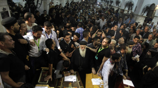 Egyptian mourners gather in front of the coffins of of several Copt Christians who were killed late Sunday, during their funeral in Warraq's Virgin Mary church in Cairo, Egypt, Monday, Oct. 21, 2013. Egypt's Christians were stunned Monday by a drive-by shooting in which masked gunmen sprayed a wedding party outside a Cairo church with automatic weapons fire, killing several, including two young girls, in an attack that raised fears of a nascent insurgency by extremists after the military's ouster of the president and a crackdown on Islamists. (AP Photo/Khalil Hamra)