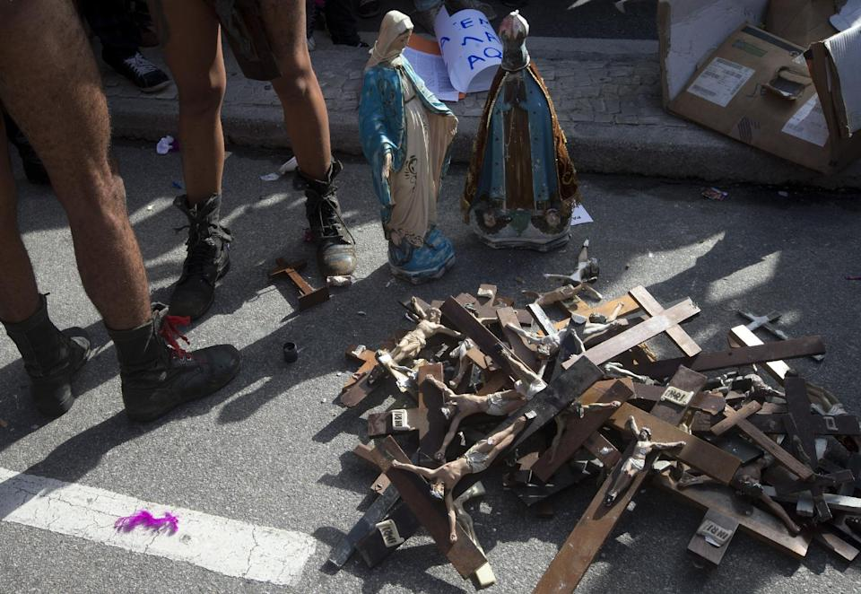 Crucifix lay on the road next to Virgin Mary statues to be used by protesters against religion on Copacabana beach near the site of a vigil during World Youth Day celebrations attended by Pope Francis in Rio de Janeiro, Saturday, July 27, 2013. (AP Photo/Silvia Izquierdo)