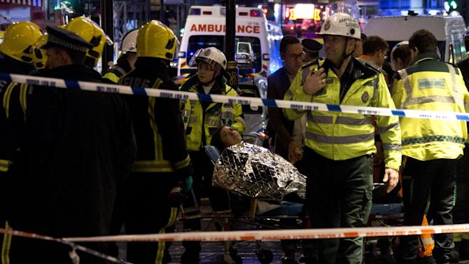 "A woman lies on a stretcher surrounded by rescue workers, awaiting evacuation following an incident during a performance at the Apollo Theatre, in London's Shaftesbury Avenue, Thursday evening, Dec. 19, 2013, with police saying there were ""a number"" of casualties. It wasn't immediately clear which part of the building had collapsed. The London Fire Brigade said the theatre was almost full, with around 700 people watching the performance. A spokesman added: ""It's thought between 20 and 40 people were injured."" (AP Photo by Joel Ryan, Invision)"