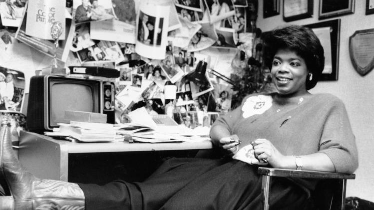"""FILE - In this Dec. 18, 1985 file photo, television talk-show host Oprah Winfrey puts her feet up as she relaxes in her studio office following a morning broadcast in Chicago, Ill. Winfrey came to Chicago in 1984 to WLS-TV's morning talk show, """"A.M. Chicago."""" A month later the show was No. 1 in the market. A year later it was renamed """"The Oprah Winfrey Show."""" Winfrey's talk show, which has taped in Chicago for 25 years, ends May 25, 2011. (AP Photo/Charlie Knoblock, File)"""