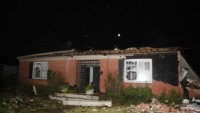A home in the Midtown section of Mobile, Ala. is damaged after a tornado touched down Tuesday, Dec. 25, 2012. A Christmas Day twister outbreak left damage across the Deep South while holiday travelers in the nation's much colder midsection battled sometimes treacherous driving conditions from freezing rain and blizzard conditions. (AP Photo/AL.com, Mike Kittrell)  MAGS OUT