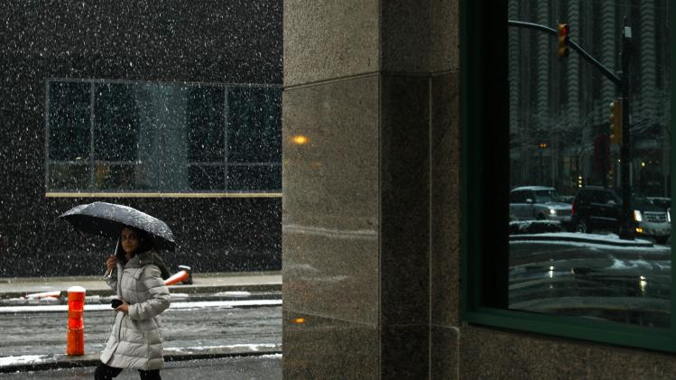 A woman walks under the snow during the arrival of a snowstorm in Exchange Place, New Jersey
