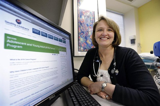 In this Monday, Feb. 25, 2013 photo, Dr. Rebecca Johnson, a cancer specialist at Seattle Children's Hospital, poses in an exam room at the hospital in Seattle. Johnson is the lead author of a new study that shows that advanced breast cancer cases have increased slightly among young women, a 34-year analysis suggests, raising many questions about possible reasons even as the disease remains uncommon in women younger than 40. Johnson herself was diagnosed with early-stage breast cancer at age 27, 17 years ago. Unlike women in the study, Johnson's cancer was caught early. (AP Photo/Elaine Thompson)