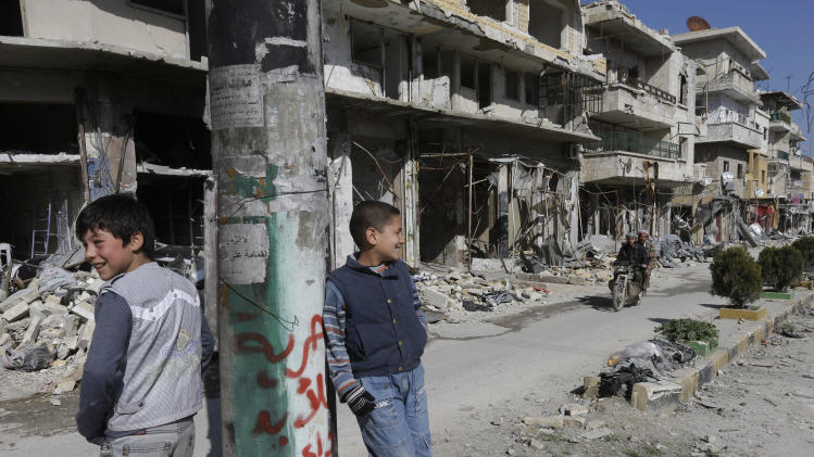 "Syrian boys, stand in  a destroyed street which was damaged by the shelling of the Syrian forces, at Maarat al-Nuaman town, in Idlib province, Syria, Tuesday Feb. 26, 2013. Syrian rebels battled government troops near a landmark 12th century mosque in the northern city of Aleppo on Tuesday, while fierce clashes raged around a police academy west of the city, activists said. the Arabic words read:""Freedom for ever"".  (AP Photo/Hussein Malla)"