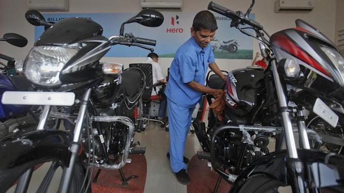 A worker cleans a bike inside a Hero MotoCorp showroom in Mumbai