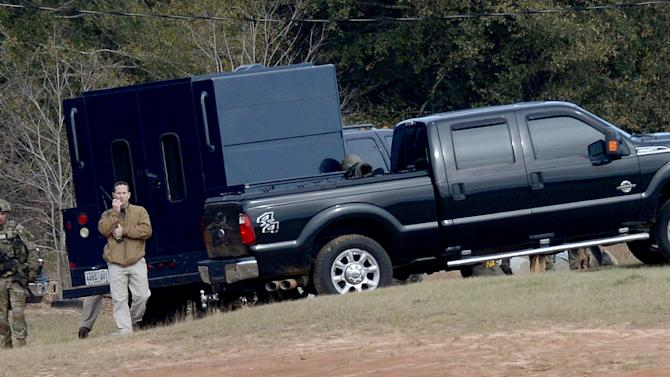 Law enforcement officials continue to work the scene of the hostage crisis in Midland City, Ala., Friday, Feb. 1, 2013. Local, state and federal officers wait out a man accused of shooting and killing a school bus driver, then snatching a 5-year-old child. Suspect Jimmy Lee Dykes has been holed up in a bunker on his property with the child since the late afternoon shooting on Tuesday, Jan. 29, 2013. (AP Photo/al.com, Julie Bennett)