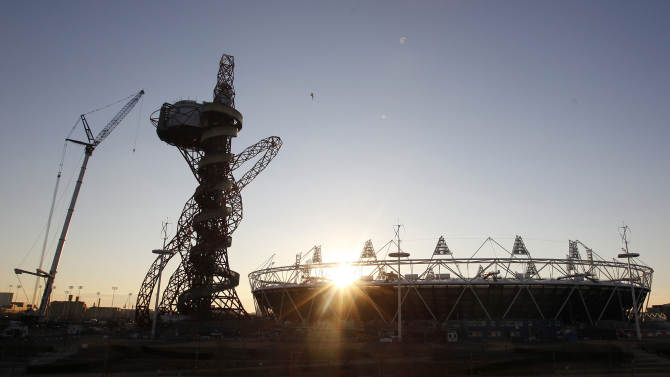 File - The London 2012 Olympic Stadium is seen at about sunset, with the partially completed ArcelorMittal Orbit  at the Olympic Park in London, in this Thursday, Feb. 23, 2012 file photo. London's Legacy Development Corporation says the ArcelorMittal Orbit will be decked in 250 color spotlights that will make it a ''beacon of east London.'' The lights will be wound through the 114.5 meter (375 foot) tower and become the center of a 15-minute nightly light show. The corporation says the effects will be tested over the next two weeks. The ruby red tower that vaguely resembles a squashed roller coaster sits beside Olympic Stadium inside the Stratford park. It is hoped it will become a major tourist attraction once the July 27-Aug. 12 games draw to a close.(AP Photo / Alastair Grant, file)
