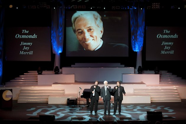 "From left, Jay Osmond, Merrill Osmond, and Jimmy Osmond sing at Andy Williams' memorial service at the Moon River Theater, in Branson, Mo., Sunday, Oct. 21, 2012. Williams, known for singing ""Moon River"" and his Christmas television specials, passed away Sept. 25. (AP Photo/Grant Hindsley)"