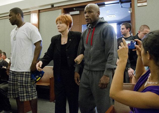 Floyd Mayweather Jr., right, walks into court escorted by his attorney Karen Winckler, center, and 50 Cent, left, to begin his 90-day jail term, Friday, June 1, 2012, in Las Vegas. The undefeated five