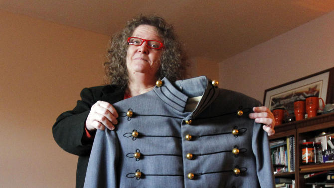 In this Dec. 20, 2012 photo, Mary Helen Taft hold up a military jacket at her home in Zimmerman, Minn. She bought the jacket at a consignment shop about 20 years ago, and the story of a similar jacket found in the debris of Superstorm Sandy prompted her to learn more about this jacket's past. With the help of the U.S. Military Academy at West Point, Taft has learned that the 80-year-old tunic was once worn by 1971 West Point graduate Joseph Francis Albano. (AP Photo/Genevieve Ross)