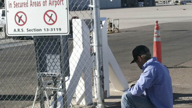 An unidentified worker makes repairs to a gate at Phoenix Sky Harbor International Airport Friday morning, Nov. 16, 2012, after a woman driving with a small child in her car crashed through the gate and drove on a runway Thursday night.  The incident was the latest in a series of similar mishaps across the country that have raised questions whether the nation's airports are truly secure. (AP Photos/Jacques Billeaud)