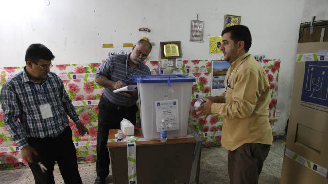 Iraqi election officials check the seals on a ballot box before the country's provincial elections at a polling center in Baghdad, Iraq, Saturday, April 20, 2013.  Polls opened amid tight security in Iraq on Saturday for regional elections in the country's first vote since the U.S. military withdrawal, marking an important test of the country's stability. (AP Photo/ Khalid Mohammed)