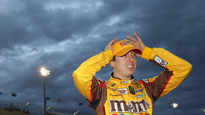 Kyle Busch checks results on a scoreboard after climbing out of his No. 18 car and setting the pole during qualifying for the NASCAR Sprint Cup Series auto race, Friday, Nov. 9, 2012, at Phoenix International Raceway in Avondale, Ariz. (AP Photo/Paul Connors)
