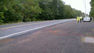 Paint marks on the road show where a dump truck flipped, pinned and killed a flag man Thursday.
