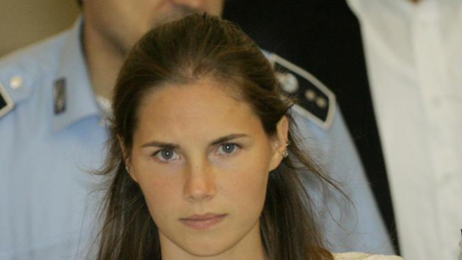 FILE - In this Tuesday Sept. 16, 2008 file photo, then murder suspect Amanda Knox is escorted by Italian penitentiary police officers from Perugia's court after a hearing, central Italy. Amanda Knox was waiting anxiously Monday, March 25, 2013 in Seattle to hear if she will face trial again as Italy's top criminal court considered whether to overturn her acquittal in the murder of her roommate in Italy. Italian prosecutors have asked the high court to throw out the acquittals of Knox and her Italian ex-boyfriend in the murder of 21-year-old British student Meredith Kercher and order a new trial. The court's decision has been postponed to Tuesday.(AP Photo/Antonio Calanni, File)