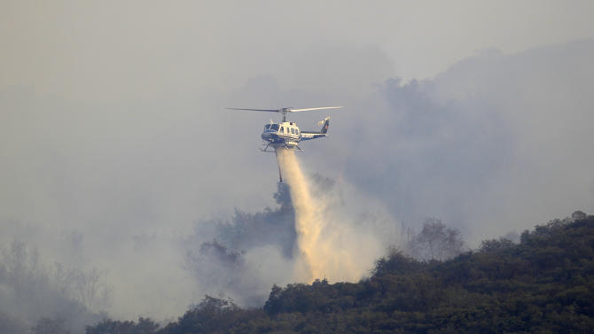 A helicopter drops fire retardant on a brush fire that started on Camp Pendleton when a Marine helicopter crashed Monday Sept. 19, 2011 in De Luz, Calif.  (AP Photo/Lenny Ignelzi)