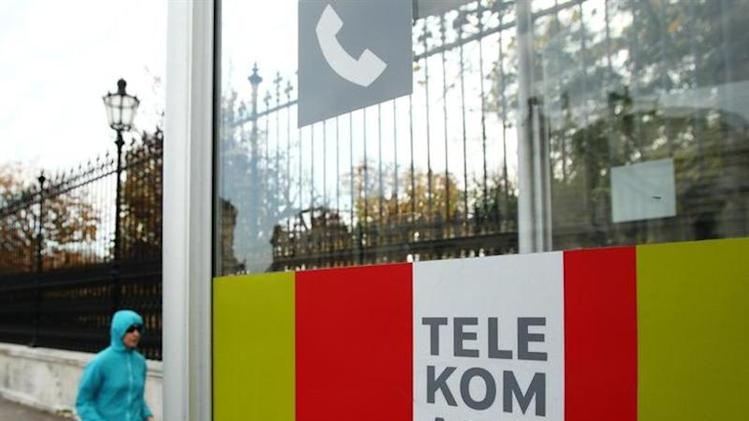 A jogger runs by a Telekom Austria phone booth in Vienna