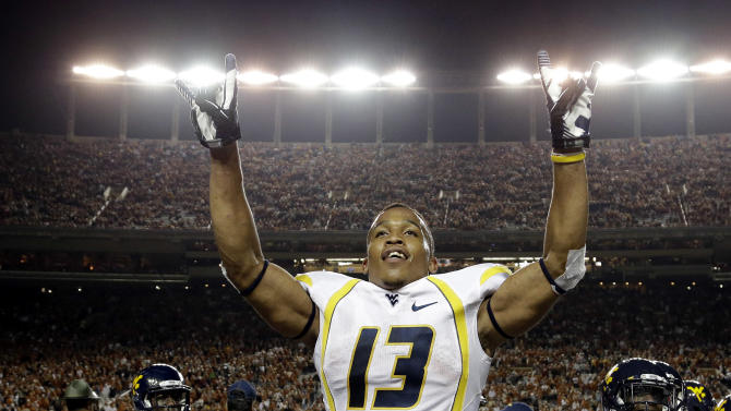 West Virginia's Andrew Buie reacts after scoring against Texas during the fourth quarter of an NCAA college football game on Saturday, Oct. 6, 2012, in Austin, Texas. West Virginia won 48-45. (AP Photo/Eric Gay)