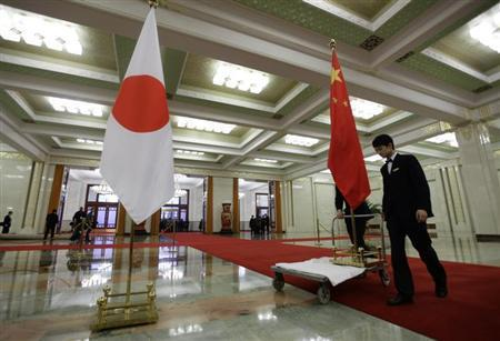 Staff from the Great Hall of the People prepare to remove Japanese and Chinese national flags after a welcome ceremony in Beijing