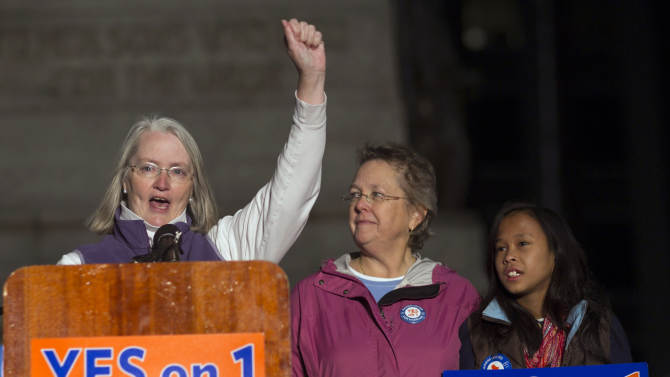 FILE - In this Nov. 1, 2012 file photo, Sarah Dowling, left, speaks at a gay marriage rally, accompanied by her partner of 18 years, Linda Wolfe, and their daughter, Maya Dowling-Wolfe, in Portland, Maine.  Dowling and Wolfe plan to marry after Maine passed a law allowing same-sex marriage, which takes effect at 12:01 a.m., Saturday, Dec. 29, 2012. (AP Photo/Robert F. Bukaty, File)