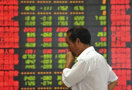 An investor stands in front of an electronic board showing stock information at a brokerage house in Fuyang