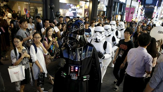 """Workers dressed as Darth Vader and Storm Trooper from """"Star Wars"""" march on a street at Myeongdong shopping district in Seoul"""