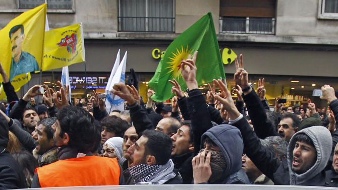 Kurdish people react as three bodies of the killed Kurdish women are taken out of the building in Paris, Thursday Jan. 10, 2012. Police say three Kurdish women have been shot dead at a pro-Kurdish centre in Paris in what the French interior minister is calling an execution. (AP Photo/Remy de la Mauviniere)
