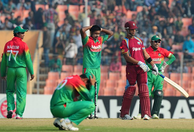 Bangladesh cricket captain Mushfiqur Rahim (R) and teammate Abul Hasan (C) react as West Indies batsman  Lendl Simmons (2R) looks on during the first one day international cricket match between Bangla
