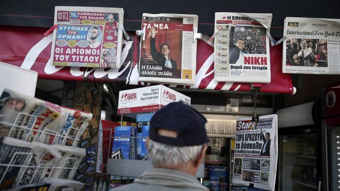 People read newspaper headlines on the results of the parliamentary elections in Athens