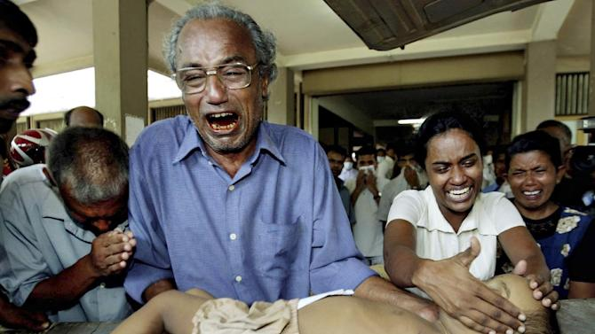 FILE - In this Monday, Dec. 27, 2004 file photo, a young tsunami victim's father cries along with other family members as he holds the body of his son at the hospital in Galle, Sri Lanka. Some 230,000 people were killed in the Indian Ocean tsunami set off by a magnitude 9.1 earthquake on Dec. 26, 2004. A dozen countries were hit, from Indonesia to India to Africa's west coast. Scores of Associated Press journalists covered the disaster, and as the 10th anniversary approached, the AP asked several of them to describe the images that have stuck with them the most. (AP Photo/Vincent Thian)