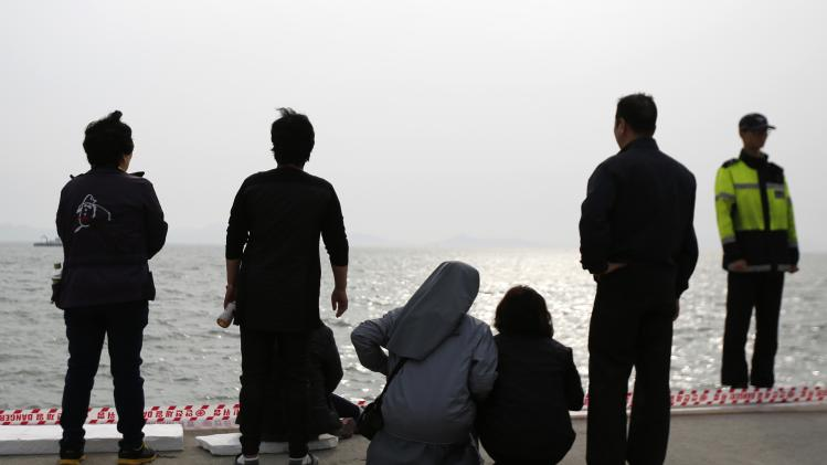 A family member (4th L) of a missing passenger on the South Korean ferry Sewol which sank in the sea off Jindo, escorted by a nun (3rd L), cries as she looks at the sea, at a port where family members of missing passengers gathered in Jindo