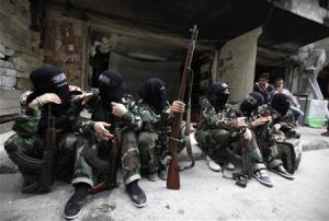 "Female members of the ""Mother Aisha"" battalion sit together along a street in Aleppo's Salaheddine district"
