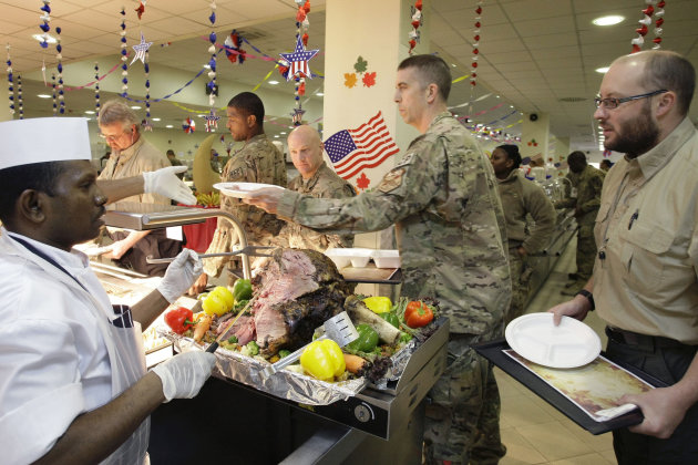 A dining facility worker, left, serves meat to soldiers and civilians for their Thanksgiving meal at the U.S.-led coalition base in Kabul, Afghanistan, Thursday, Nov. 22, 2012. The dining hall at the U.S.-led coalition base in the Afghan capital served up mac-and-cheese along with traditional Thanksgiving Day fixings.