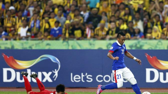 Malaysia's Zubir controls the ball against Thailand's Chappius during their Suzuki Cup final soccer match at Bukit Jalil stadium in Kuala Lumpur