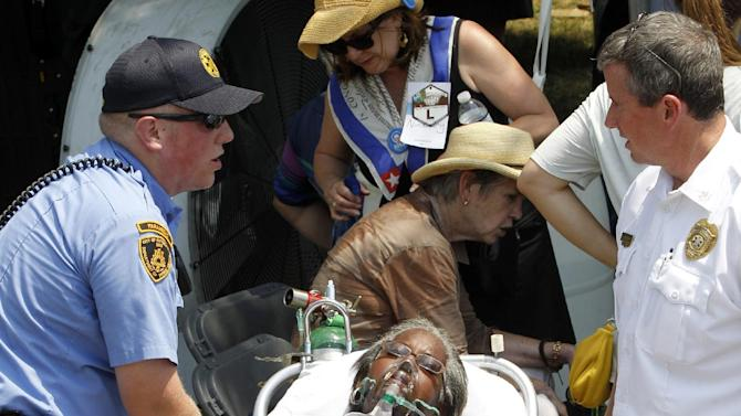A woman is taken away on a stretcher after  being effected by the heat while waiting for President Barack Obama at Carnegie Mellon University in Pittsburgh, Friday, July 6, 2012. Obama is on a two-day bus campaign trip through Ohio and Pennsylvania  (AP Photo/Keith Srakocic)