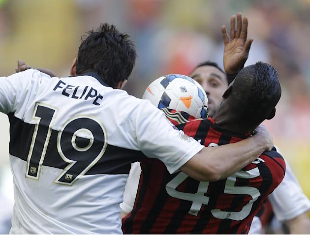 AC Milan forward Mario Balotelli, right, challenges for the ball with Parma midfielder Felipe of Brazil during a Serie A soccer match between AC Milan and Parma, at the San Siro stadium in Milan, Ital