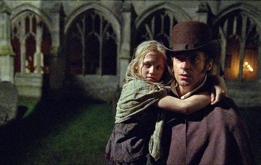 """This film image released by Universal Pictures shows Hugh Jackman as Jean Valjean holding Isabelle Allen as Young Cosette in a scene from """"Les Miserables."""" (AP Photo/Universal Pictures, Laurie Sparham)"""