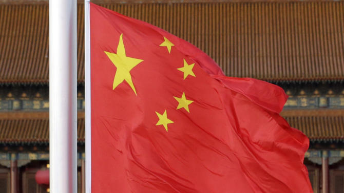 Chinese paramilitary policemen lower a Chinese national flag near a portrait of former Chinese leader Mao Zedong during the 18th Chinese Communist Party Congress held at Tiananmen Square in Beijing, China, Tuesday, Nov. 13, 2012. (AP Photo/Lee Jin-man)
