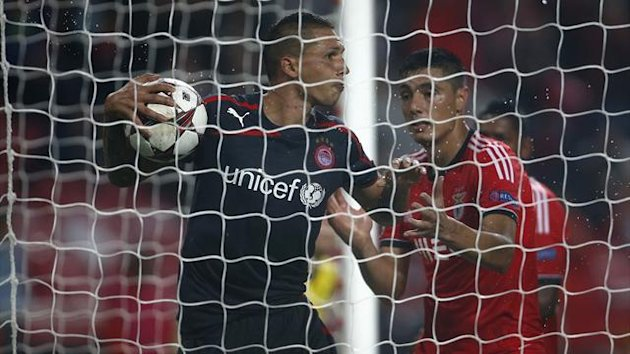 Benfica's Oscar Cardozo (R) tries to take the ball from Olympiakos' Jose Holebas after scoring a goal during their Champions League soccer match at Luz stadium in Lisbon October 23, 2013 (Reuters)